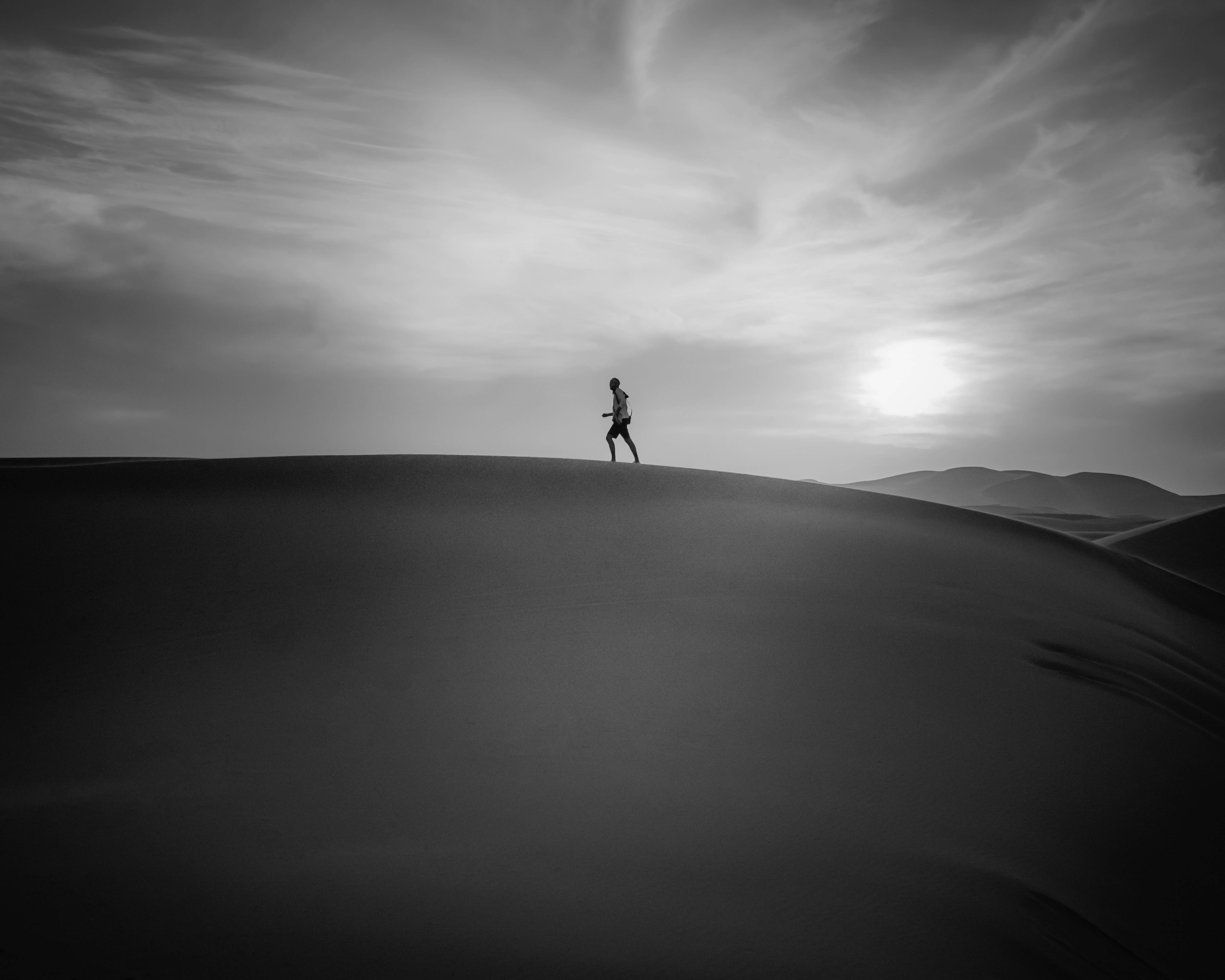 grayscale photography of man running on desert field during daytime